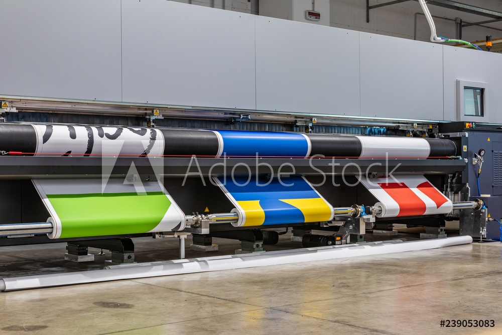 Very big printer during color sample phase, massive vinyl rolls, digital press technology, out of standard large advertising production. Automated process concept.