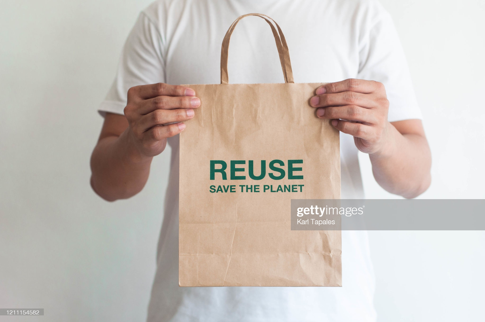 """A front view of a young man holding a reusable paper bag with phrase """"reuse, save the planet"""""""