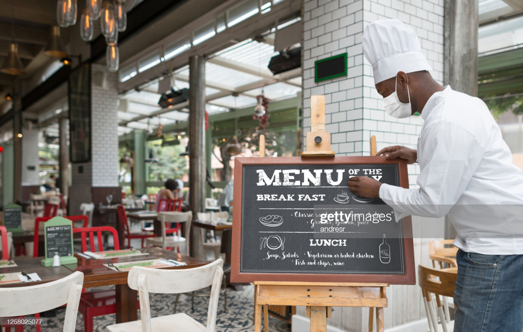 Happy African American chef writing the menu at a restaurant while wearing a facemask during the COVID-19 pandemic - reopening of business concepts **DESIGN OF MENU WAS MADE FROM SCRATCH BY US**