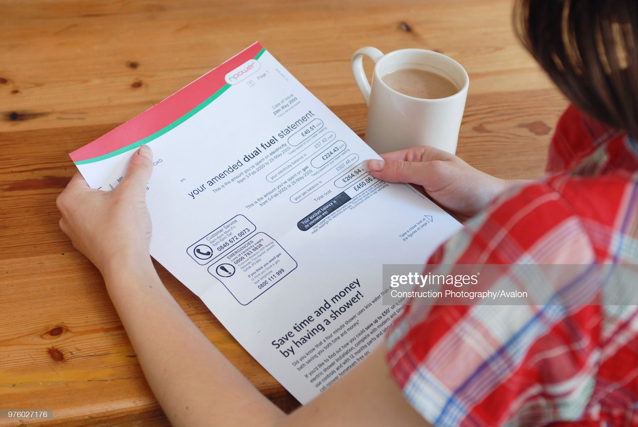 Young person looking at utility bill. (Photo by David Potter/Construction Photography/Avalon/Getty Images)